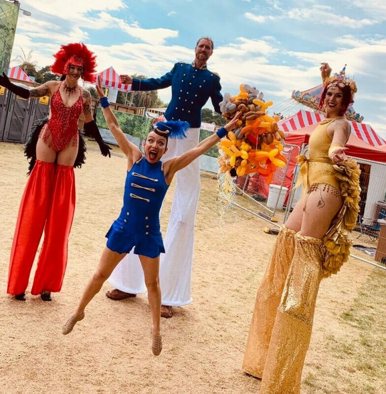 The Best Greatest Showman Theme Party Performers at Hyde Park. Three stiltwalkers in circus showgirl and ringmaster outfits with jumping ringmistress in front