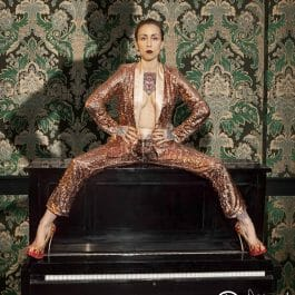 cabaret performer in gold suit sitting on piano in a dramatic pose in Brighton show