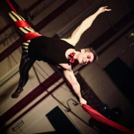 aerial silks performer as modern clown with upside down hold