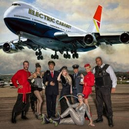 The cast of the Come Fly With Me comedy cabaret on the tarmac with the Electric Cabaret Company plane flying over them