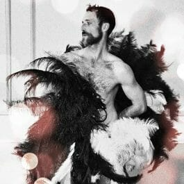 Male fan dancer and Boylesque artist holding two large feather fans