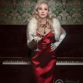 glamorous burlesque performer in red silk dress and white gloves with 1940's waved long blonde hair with drink in hand