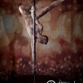 male pole dancer in glittery briefs holding dramatic upside down pole