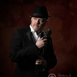 vintage male lounge singer in suit and trilby with retro style microphone