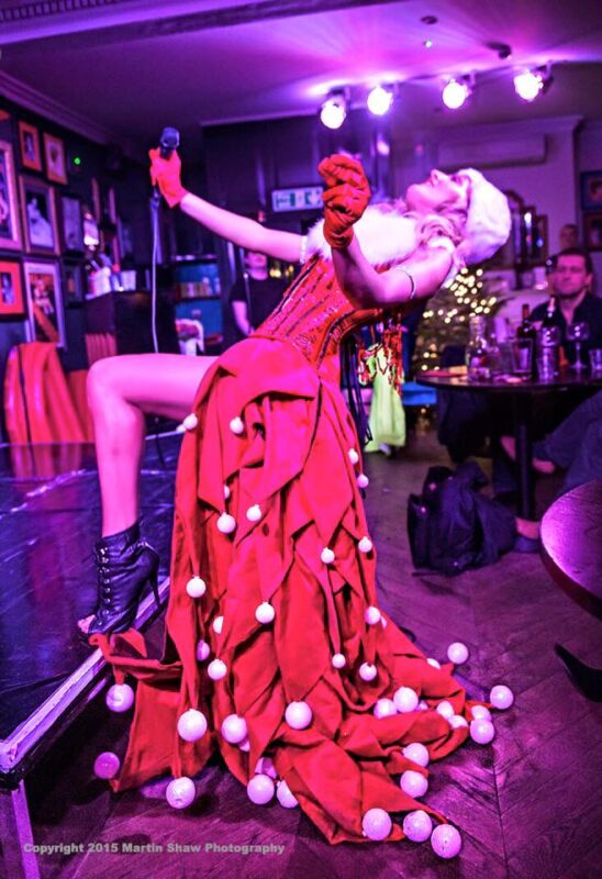Electric Cabaret Company Christmas entertainment Singer in Christmas costume made of red and white Santa hats