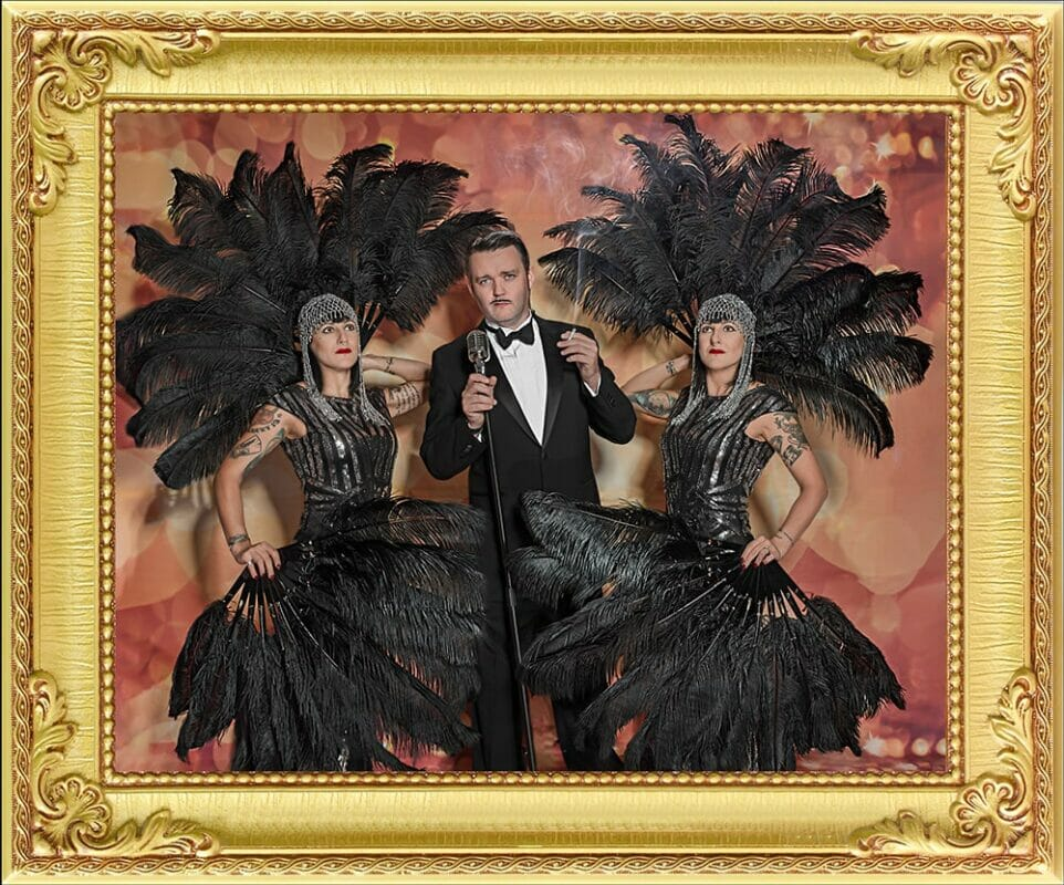 1920's lounge singer performer in tuxedo from our event management & entertainment agency in London and Brighton with 2 glamorous twin feather dancers either side at a stage show in Brighton