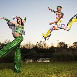 fairy tale style performers jump in the air one on bouncy stilts and one on normal stilts at summer party outdoors