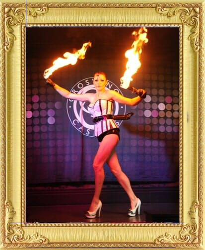 One of our cabaret performers for hire in Brighton and London, broken doll fire performer holding two flaming fire sticks on stage at cabaret show in Brighton