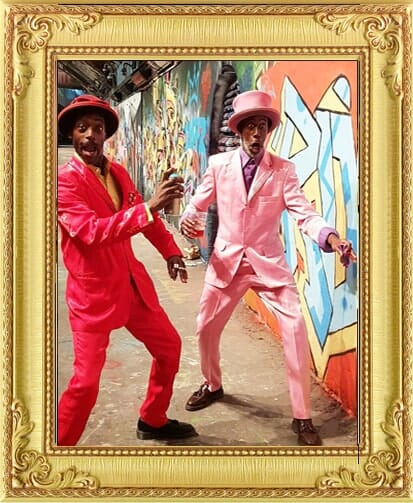 Performers for Hire Brighton & London, colourful modern clown performers, one in pink suit and one in red suit strike crazy poses in graffiti tunnel in London