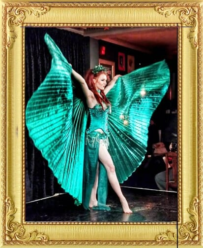Burlesque performers for hire with giant green isis wings and green evening dress raising wings in glamorous pose on stage performing in shows in London and Brighton