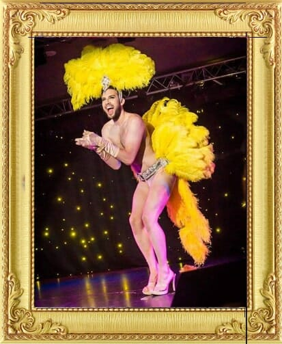 Our Burlesque performers for hire include this Burlesque showboy in yellow feathers and heels performs on stage in Brighton and London
