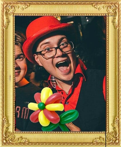One of our circus acts for hire in London and Brighton, laughing balloon modeller modern clown circus act with balloon flower and red shirt, bowler hat and black waistcoat at theme event in Brighton