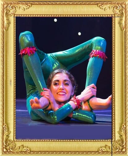 One of our circus acts for hire in London and Brighton, stunning contortionist in green shiny costume bends into an extreme position on stage in London
