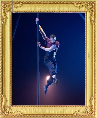 One of our circus acts for hire in London and Brighton, acrobatic man performs on swinging pole and swings around it wearing old fashioned trousers and top in London circus
