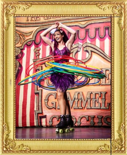 One of our circus acts for hire in London and Brighton, circus act roller skating with multiple hula hoops in sequin costume and tutu in big top at Brighton