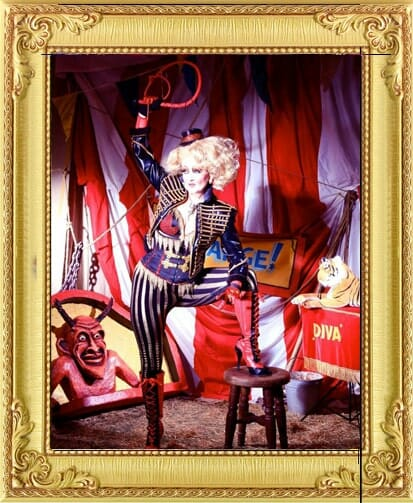One of our circus acts for hire in London and Brighton, this whip cracking circus act with a crazy costumed ring mistress with giant wig and whip held in the air in stripey big top
