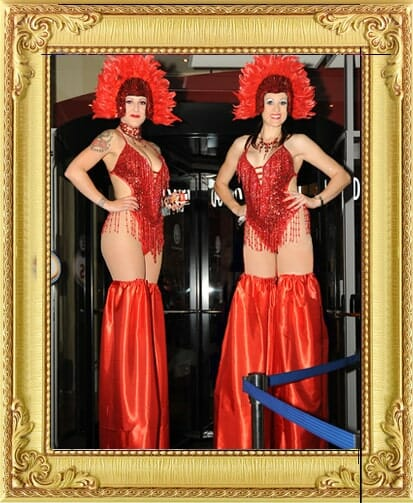 Show stopping corporate party entertainment in London and Brighton, 2 stilt-walkers in red showgirl costume pose at the entrance to a corporate party in Brighton