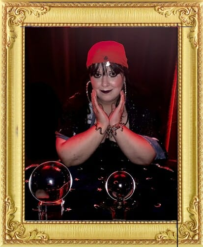 Unusual corporate party entertainment in London and Brighton, fortune teller in traditional costume and headscarf poses with 2 crystal balls as fun corporate party entertainment in Brighton