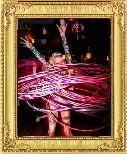 Performers for Hire Brighton & London, hula hoop performer with multiple pink hoops covering her entire body and hands in the air at nightclub event in Brighton