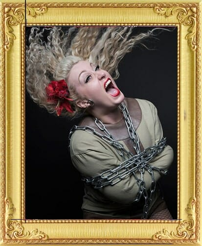 Beautiful female magician for hire in London and Brighton escapologist battles chains around her with her hair flying in the air at London magic event