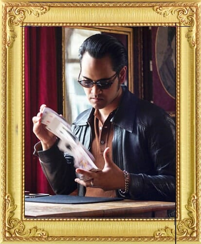 modern suave magician for hire in London and Brighton shuffles cards wearing shades and slicked back hair in Brighton show