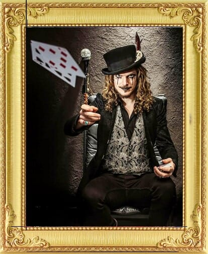 vintage sideshow style magician for hire with top hat and cane throws playing cards into the air