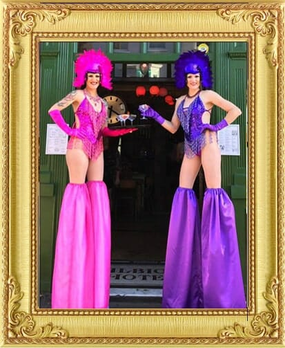 Showgirl stilt-walker performers for hire one in London and Brighton one in pink and one in purple handing out drinks at venue doorway in Brighton