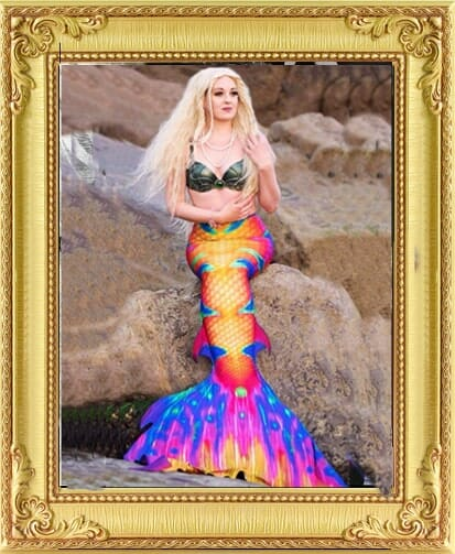 Mermaid performer sitting on rock with beautiful coloured tail and long blonde hair, a bespoke entertainment in London and Brighton.
