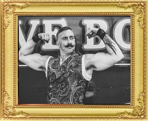 Performers for Hire Brighton & London, vintage black and white image of strongman performer with curly moustache flexing his muscles at London party