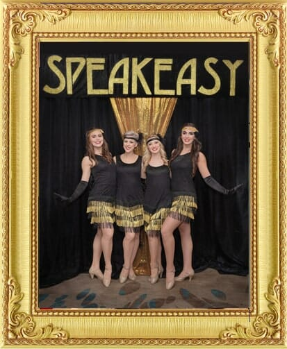 Charleston dancer performers for hire in London and Brighton wearing black and gold in front of Speakeasy sign at 1920s event in Brighton