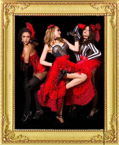 Cabaret performers for hire in Brighton and London include this trio of moulin rouge performers posing in red and black dresses on stage at London theme event