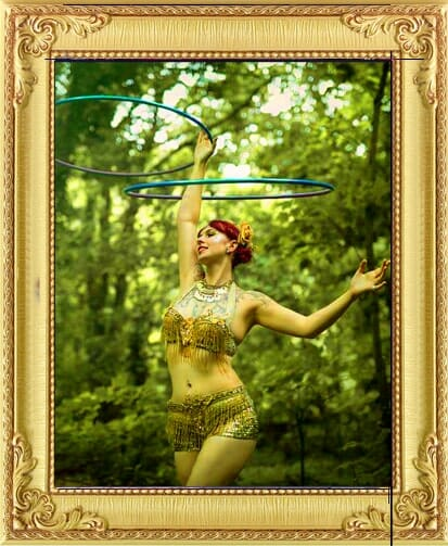 Wedding party performers for hire in Brighton and London include this beautiful lady in gold beaded costume spinning hoops above her head in outdoor wooded scenery