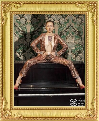 female performer available for hire from our event management & entertainment agency in gold suit sitting on a piano at cabaret venue in Brighton