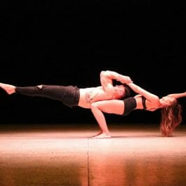 horizontal adagio or acro balance hold with female performer supporting male performers weight on stage at corporate event
