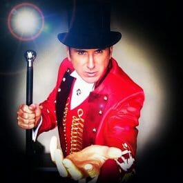 greatest showman style victorian ringmaster in red brocade jacket, top hat and cane reaches forward in dramatic stance