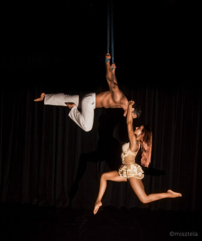 Male and female aerial performer at corporate entertainment in London wearing white outfits. Female performer holds on to male performers neck and bicycle kicks in the air.