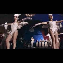 vintage show band in ballroom with showgirls in white feathered costumes dancing