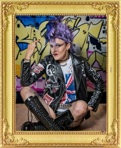 Punk rock performer sits cross legged with purple mohawk and leather jacket in front of sprayed wall for bespoke entertainment in London and Brighton.