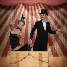 Vintage magician and assistant in top hat and tails in a red and white striped marquee