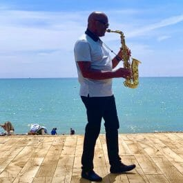walkabout saxophone player for hire. Walking on the beach playing saxophone with the blue sky and sea behind
