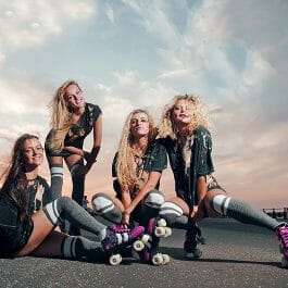 four female members of a rollerskating troupe pose in street wear at sunset