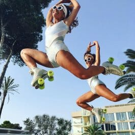 roller skating twins in white sixties outfits jump in the air at an outdoor location with palm trees