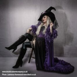 beautiful witch in purple and black feathered outfit poses on chair at show in Brighton