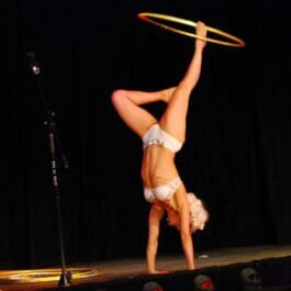 acrobat performs a handstand while spinning a hula hoop on her foot on stage in London