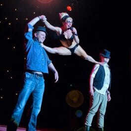 performer balances in the splits balancing on two audience members at a cabaret show in London