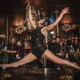 performer on the bar in the splits performs martin making trick in London