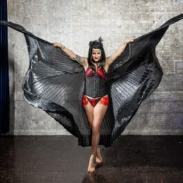 vampire queen performer with giant wings dressed in red and black performing in Brighton