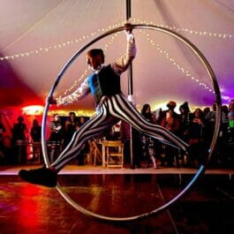 Cyr wheel performer in striped trousers performs in massive wheel in a circus tent in London and Brighton