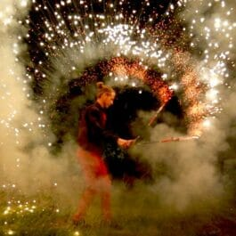 fire performer for hire spins pyrotechnic sparkling fire outdoors