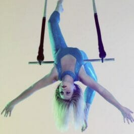 trapeze performer in a blue leotard hangs upside down from a swing in Brighton
